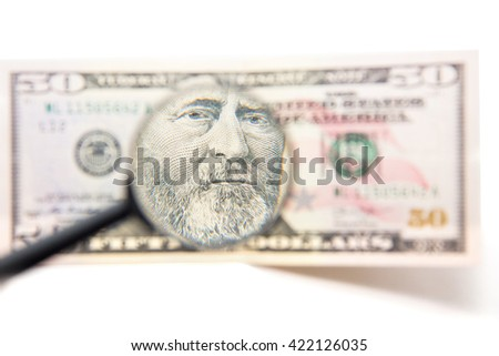 Portrait of Ulysses S. Grant on 50 US dollars under a magnifying glass. close-up isolated on white background - stock photo