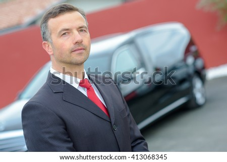 Portrait of undertaker and hearse - stock photo