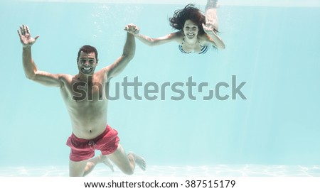 Portrait of underwater couple holding hands and enjoying in swimming pool - stock photo