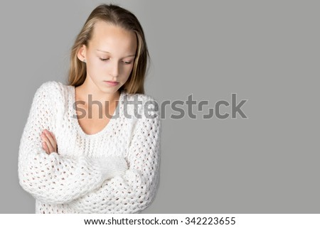 Portrait of unhappy beautiful casual caucasian girl wearing white knitted sweater, standing with crossed arms, looking down, studio image, gray background, copy space - stock photo