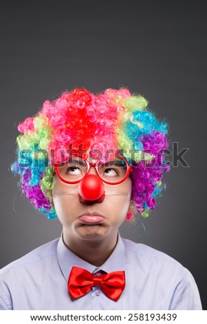Portrait of unhappy clown looking up