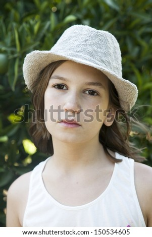 portrait of Unhappy little girl in straw hat  - stock photo