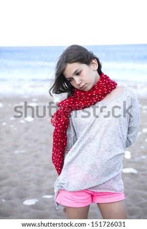 portrait of Unhappy little girl with  red scarf in spot - stock photo