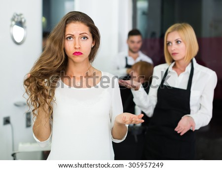 Portrait of unhappy longhaired female at the hairdressing salon - stock photo
