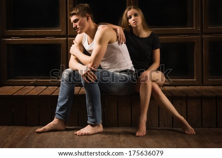 Portrait of unhappy young couple in bedroom - stock photo