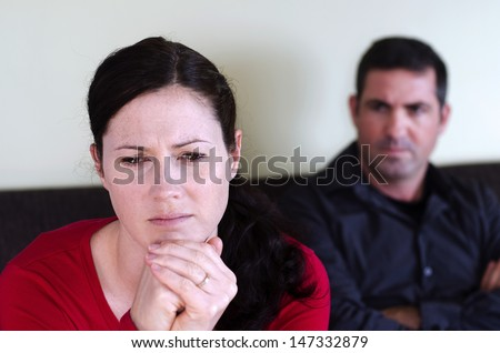 Portrait of unhappy young couple who have fallen out over a disagreement sitting on a sofa. Woman in the front and the man in the background. - stock photo