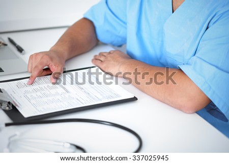 Portrait of unknown male surgeon doctor sitting at the table in hospital office, stethoscope - stock photo
