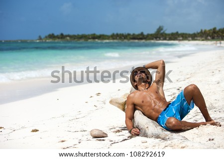 Portrait of unrecognizable young man sitting on a tropical beach