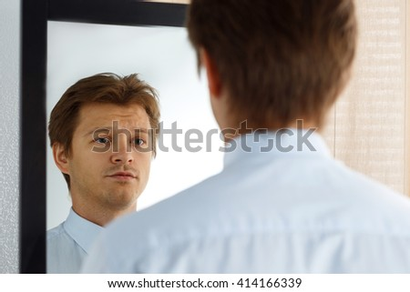 Portrait of unsure young businessman with unhappy face looking at the mirror. Man preparing for important meeting, new job interview or dating. Difficult relationship, stress management concept - stock photo