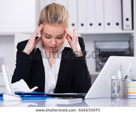 Portrait of upset businesswoman with headache working with documents in office