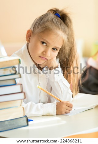 Portrait of upset girl writing test in classroom and looking at camera