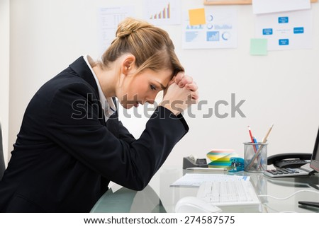 Portrait Of Upset Young Businesswoman Sitting At Desk In Office - stock photo