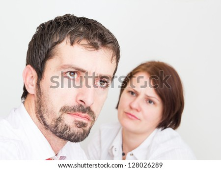 Portrait of upset young couple sitting separately in the bedroom - stock photo
