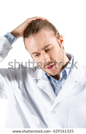 portrait of upset young doctor in white coat isolated on white