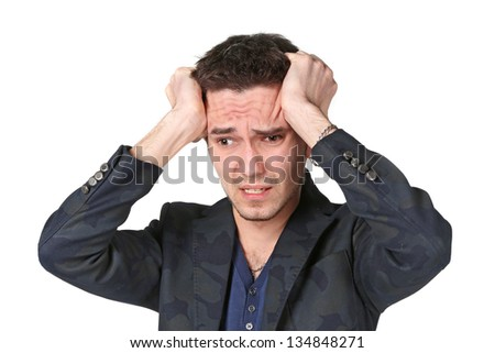 Portrait of  upset young man grabbing his head in desperation over white background - stock photo