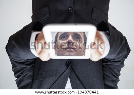 Portrait of upside down businessman with reflected face in digital tablet.