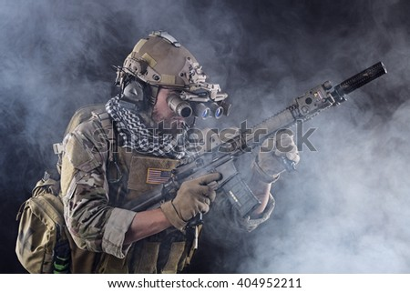 Portrait of US Army Soldier with Four-eyed night vision goggles in the Smoke; Dark and Foggy Background - stock photo