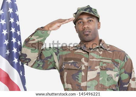 Portrait of US Marine Corps soldier saluting American flag over gray background - stock photo