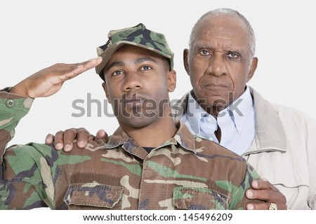 Portrait of US Marine Corps soldier with father saluting over gray background - stock photo