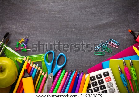 portrait of various colorful stationery on top of blackboard. ready for your design