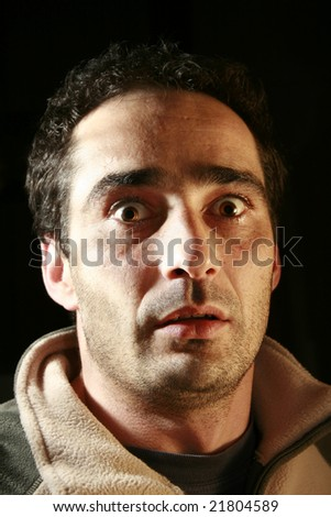 Portrait of very amazed, frightened man with open mouth. Black background. - stock photo
