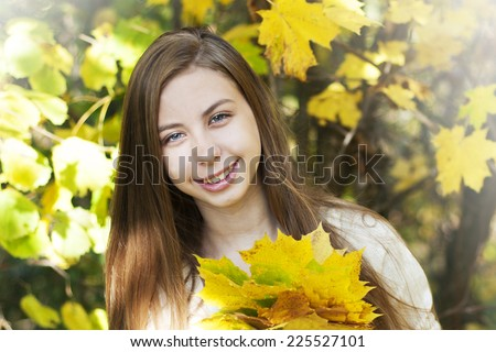 Portrait of very beautiful young girl in autumn park - stock photo