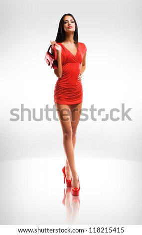 Portrait of very fashionable slender brunette beauty in red hot little dress. - stock photo