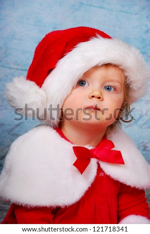 portrait of very serious baby girl  in red santa hat and dress - stock photo