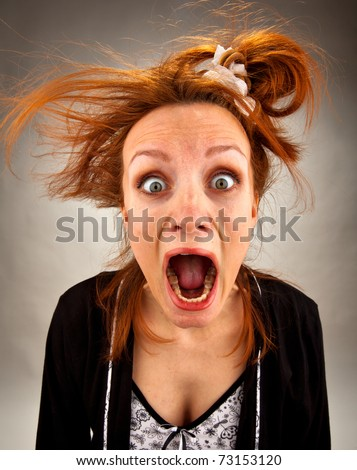 Portrait of very surprised bizarre screaming housewife - stock photo
