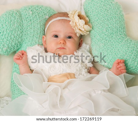 Portrait of very sweet and beautiful little baby child sitting in studio on the soft bed like a bride or princess in funny white and creamy costume with bare feet - stock photo