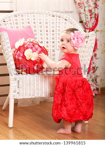 Portrait of very sweet little child sitting like a princess in funny pink and red costume