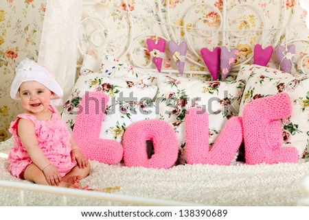 Portrait of very sweet little child sitting with words of love in funny pink costume - stock photo