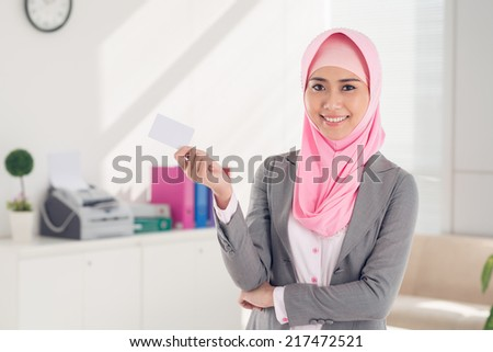 Portrait of Vietnamese business lady in hijab holding a business card - stock photo