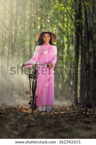 Portrait of Vietnamese girl traditional dress with bicycle - stock photo