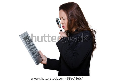Portrait of visually handicapped woman using magnifying glass to see large calculator isolated on background - stock photo