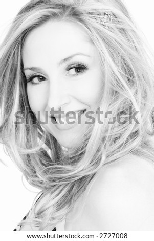 Portrait of vivacious smiling woman with tousled hair  in black and white tones.
