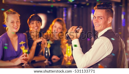Portrait of waiter and beautiful women standing at bar counter against flying colours