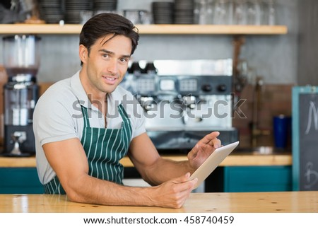 Portrait of waiter standing at counter using digital tablet