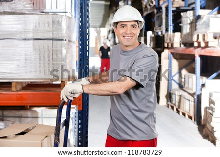 Portrait of warehouse worker pushing handtruck with cardboard boxes at warehouse - stock photo