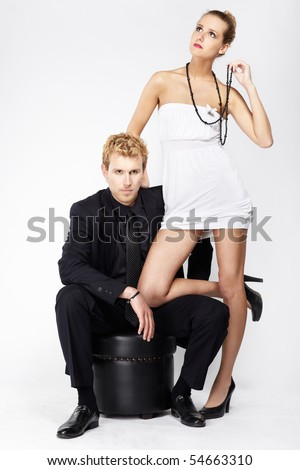 portrait of well-dressed blonde couple on gray. - stock photo