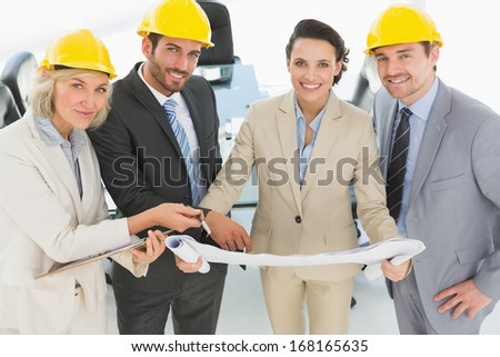 Portrait of well dressed confident architects with hard hats and blueprint standing in the office - stock photo