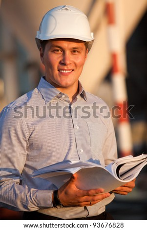 portrait of well-dressed man with documants in hard hat standing against the construction - stock photo