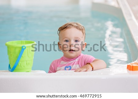 Portrait of white Caucasian baby girl playing with toys in water standing by swimming pool nosing inside, looking in camera, training to swim, healthy active lifestyle