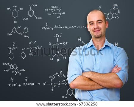 portrait of white teacher infront of blackboard - stock photo