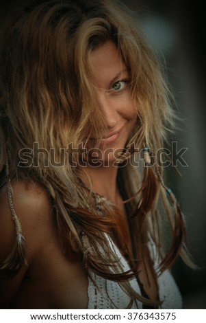 portrait of wild woman with feathers in her hair - stock photo