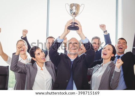 Portrait of winning business team with an executive holding a gold trophy - stock photo