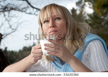 Portrait of  woman a mug of a hot drink outdoors - stock photo