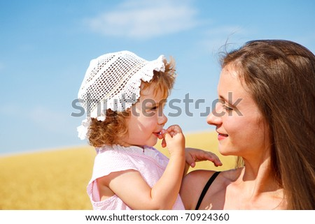 Portrait of woman and curly toddler girl in the outdoor - stock photo