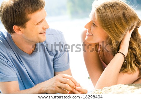 Portrait of woman and man looking at each other outside - stock photo