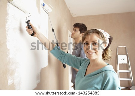 Portrait of woman and man painting wall with paint rollers - stock photo